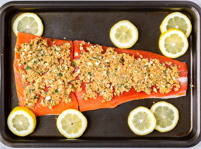 2 large salmon fillets topped with lemon garlic bread crumbs with lemon slices around them on a baking sheet