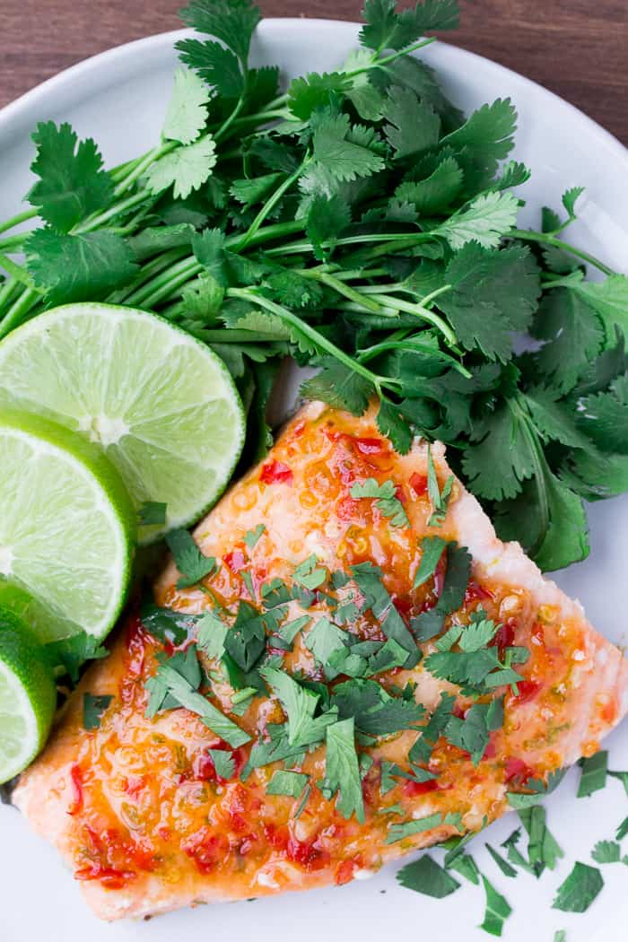 Overhead of Chili Lime Salmon Recipe on a White Plate with Limes and Cilantro