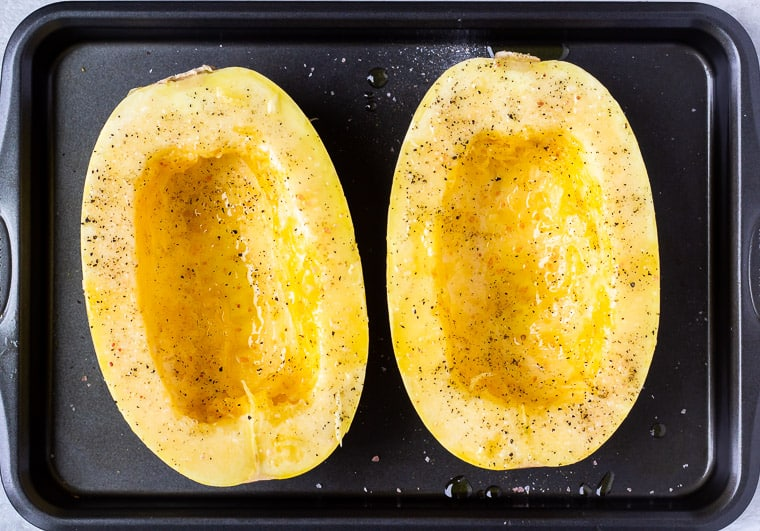 Spaghetti squash cut in half and seasoned with olive oil, salt and pepper on a baking sheet