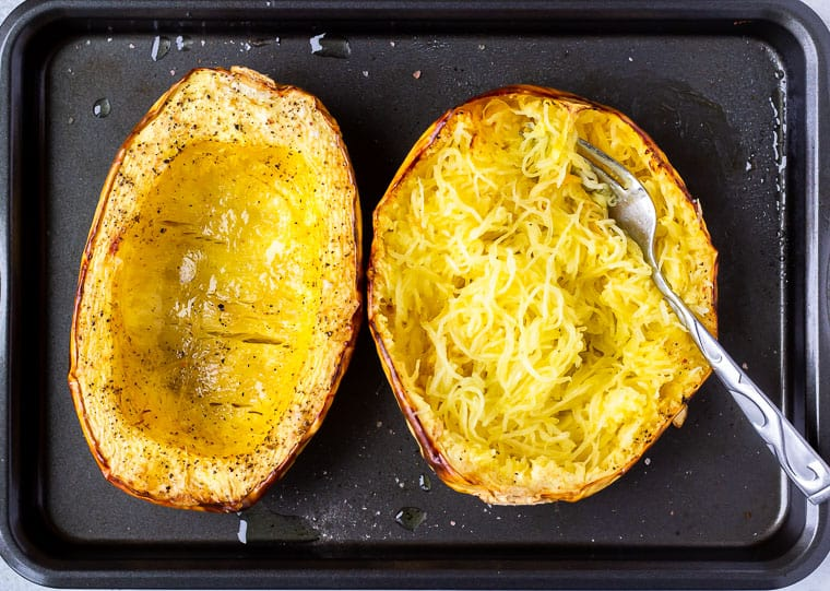 2 roasted spaghetti squash halves on a baking sheet with one scraped out with a fork to show the spaghetti-like appearance