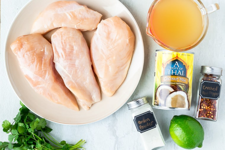 Ingredients needed to make Coconut Lime Chicken laid out on a white background