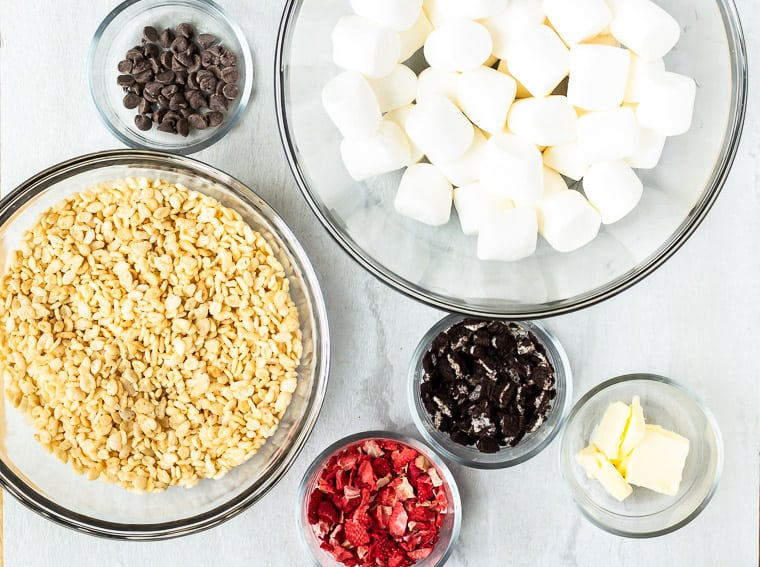 Ingredients needed to make Chocolate Covered Strawberry Rice Krispie Treats in glass bowls on a white counter