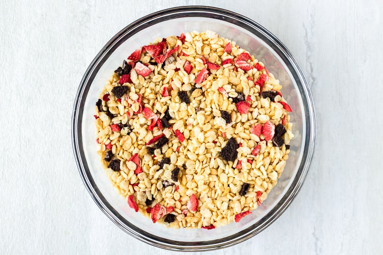 Rice Krispies, dehydrated strawberries and crushed cookies mixed together in a glass bowl over a white background