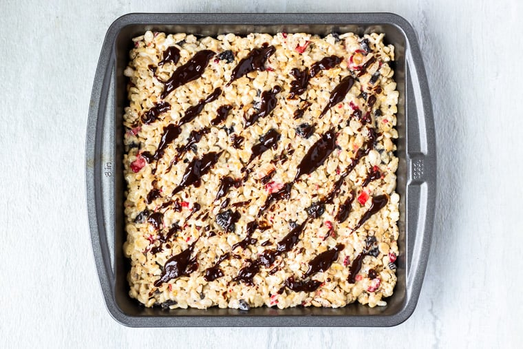 Rice krispie treats in a square baking pan with melted chocolate drizzled on top over a white background