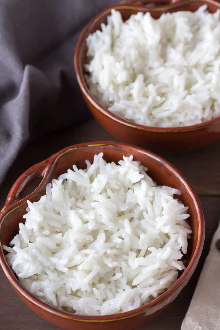 2 Brown Bowls of Coconut Rice on a Wood Backdrop with a gray napkin