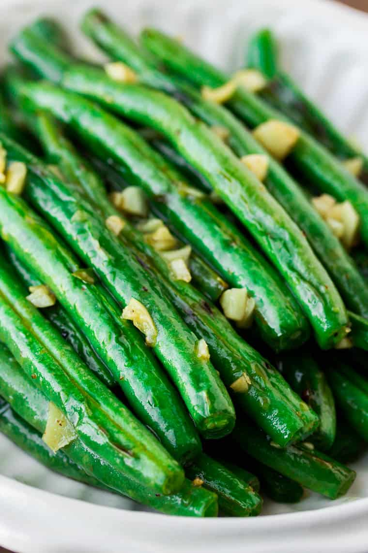 Close up of green beans with garlic in a white dish