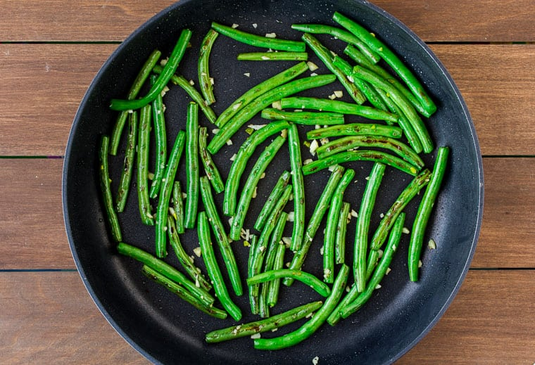Green beans and garlic in a skillet over a wood backdrop