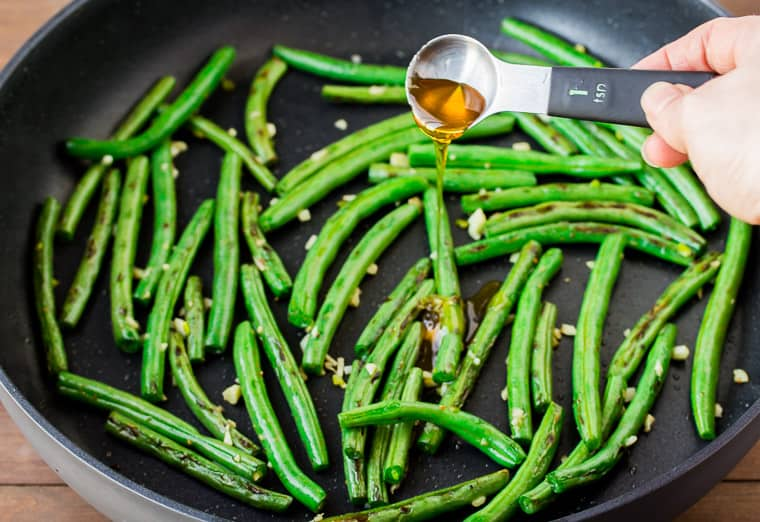 A teaspoon of honey being pour onto green beans in a black skillet