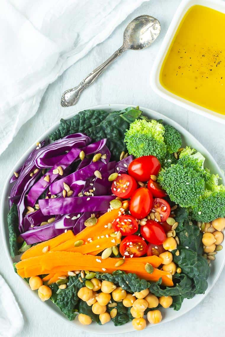 Overhead of a colorful salad with a small square bowl of dressing with a spoon and white napkin in the background