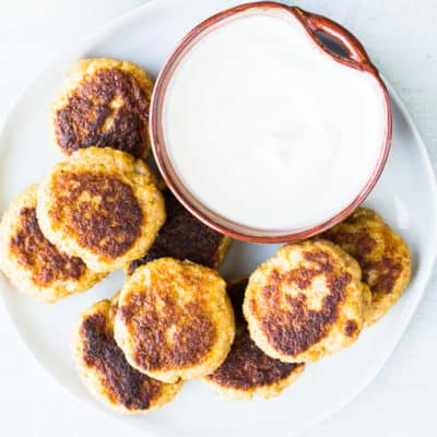 Lemon Garlic Shrimp Cakes on a white plate with a bowl of aioli on a white background