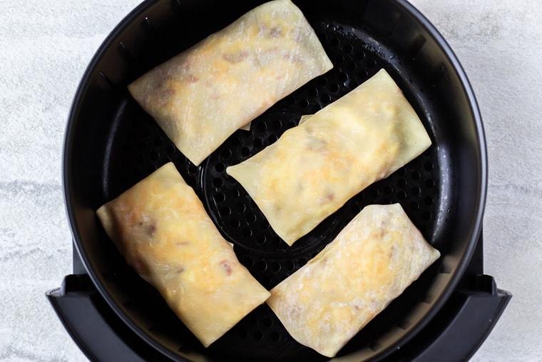 4 egg rolls in an air fryer basket