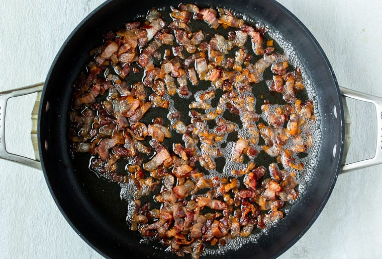 Diced bacon cooking in a black skillet