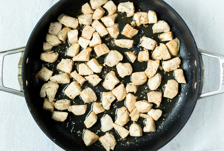 Cubed chicken cooking in a large, black skillet.