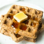 3 Flaxseed Waffles on a white plate with a white napkin and 2 white cups in the background