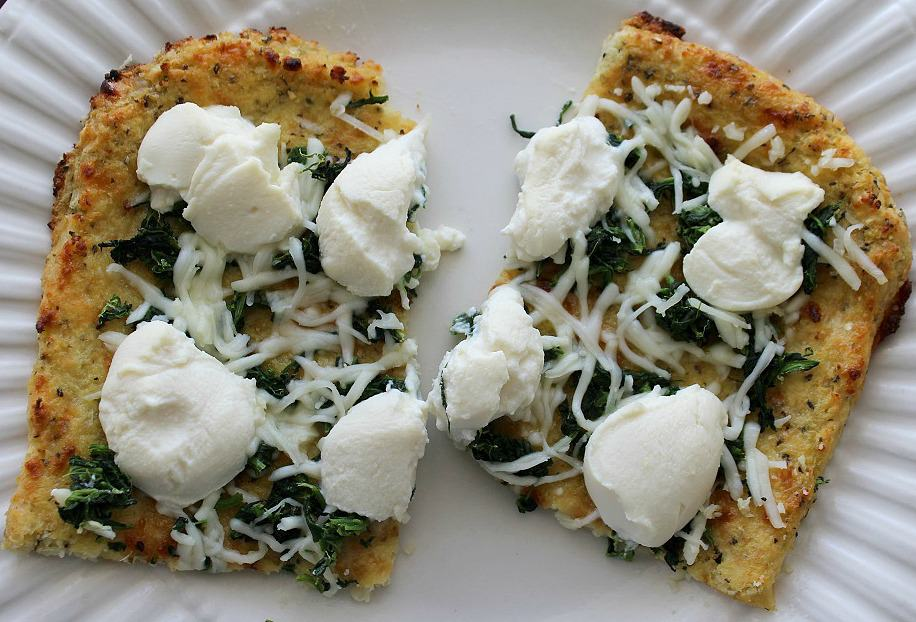 Spinach Ricotta Pizza with Roasted Garlic on a white plate