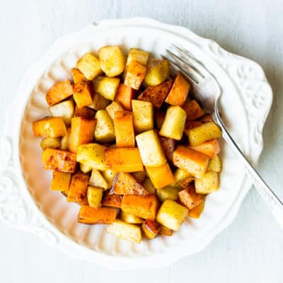 Maple Cinnamon Sweet Potatoes and Apples in a white bowl with a fork over a white background