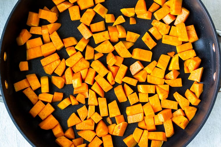 Diced sweet potatoes cooking in a black skillet