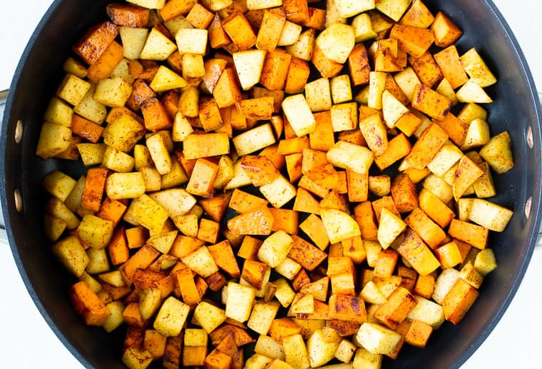 Diced sweet potatoes and apples with spices cooking in a black skillet