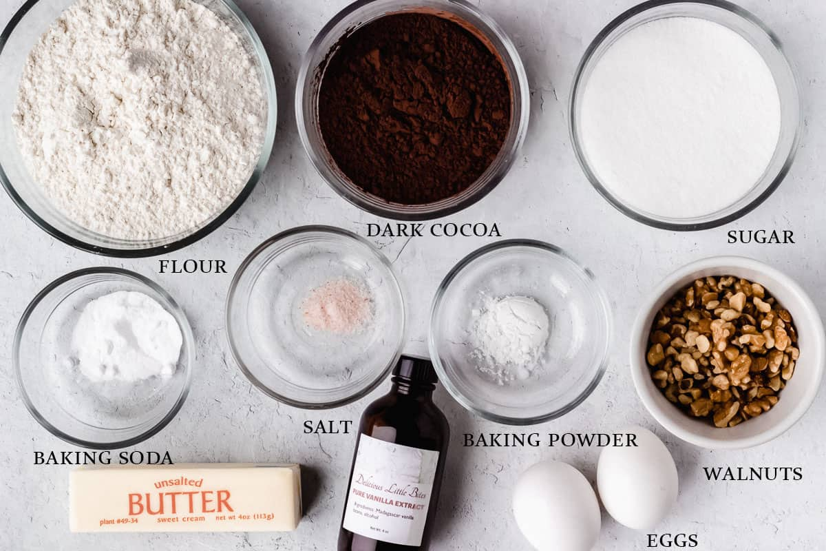 Ingredients to make dark chocolate chip walnut cookies on a white background with labels
