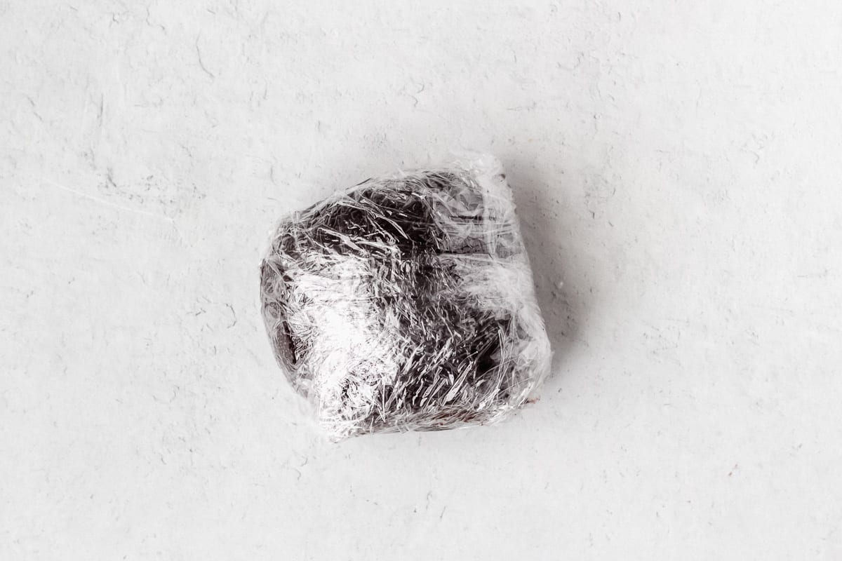 Chocolate cookie dough wrapped in plastic wrap on a white background