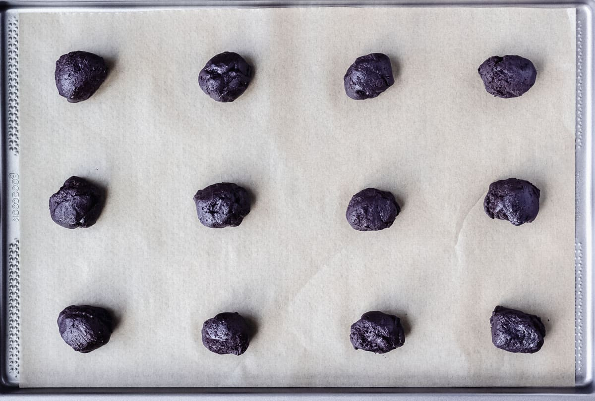 Dark chocolate cookie dough balls on a parchment paper lined baking sheet before baking