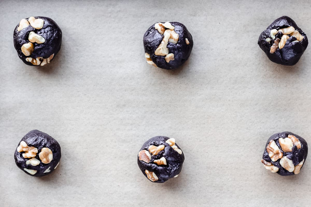 Dark chocolate cookie dough balls with chopped walnuts pressed into the tops before baking