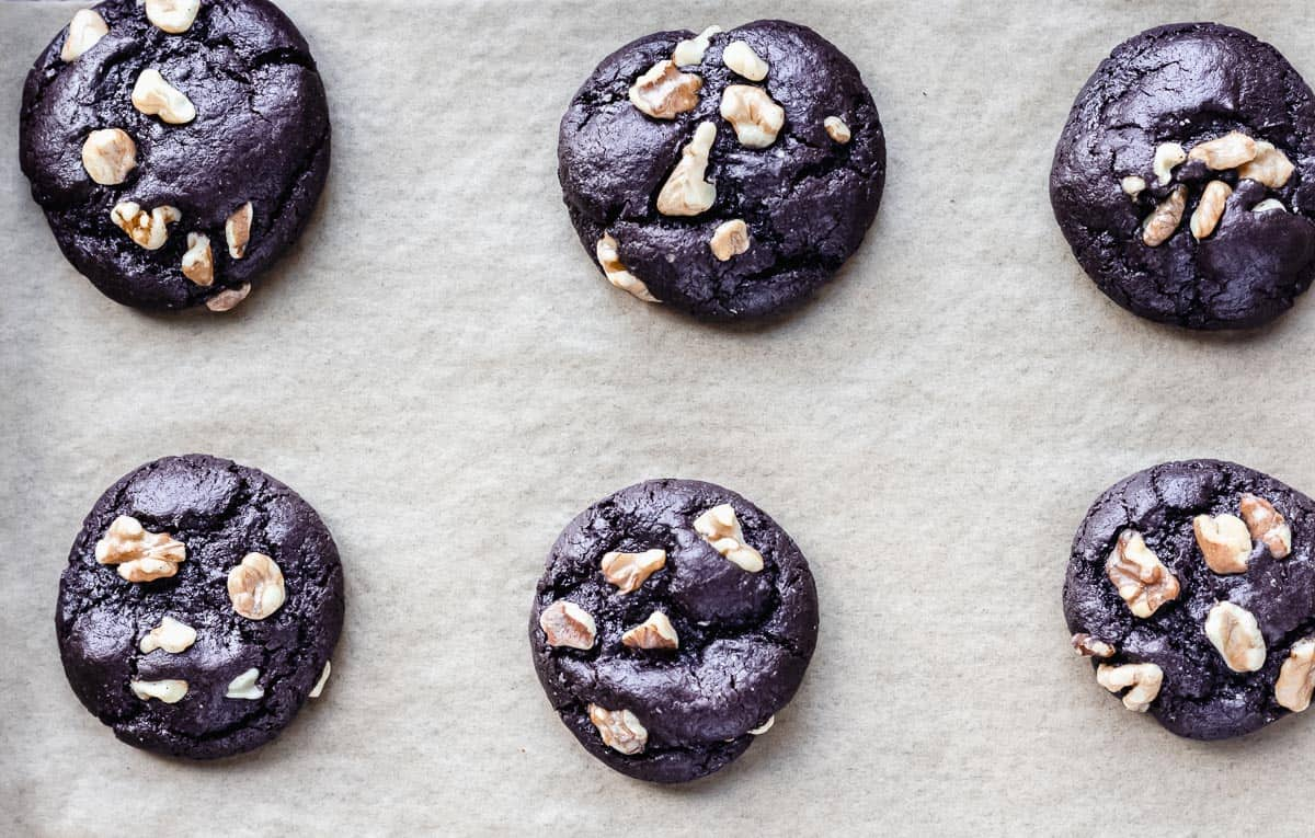 6 Baked Dark Chocolate Chip Walnut Cookies on a parchment paper lined baking sheet