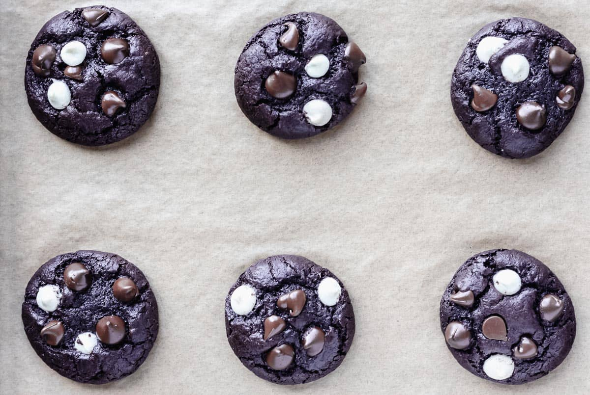 Baked triple dark chocolate chip cookies on a parchment paper lined baking sheet