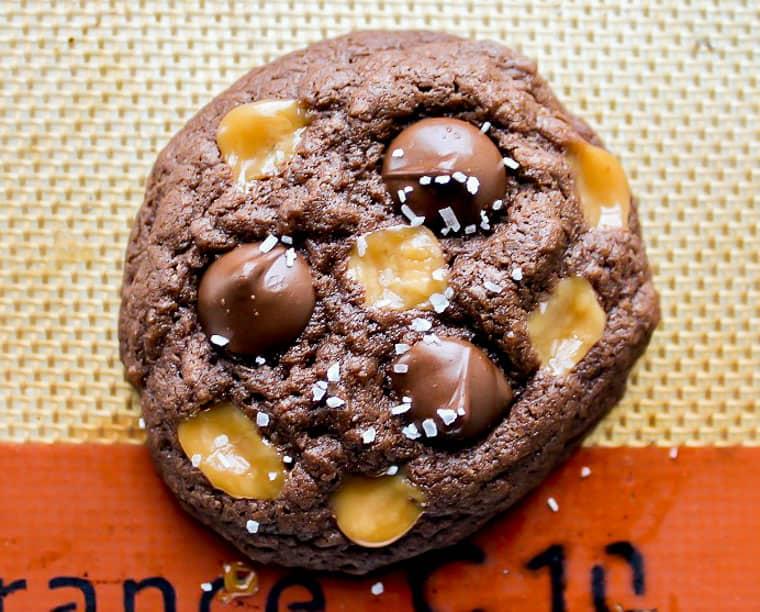 A single gluten free salted caramel cookie up close on a silpat mat