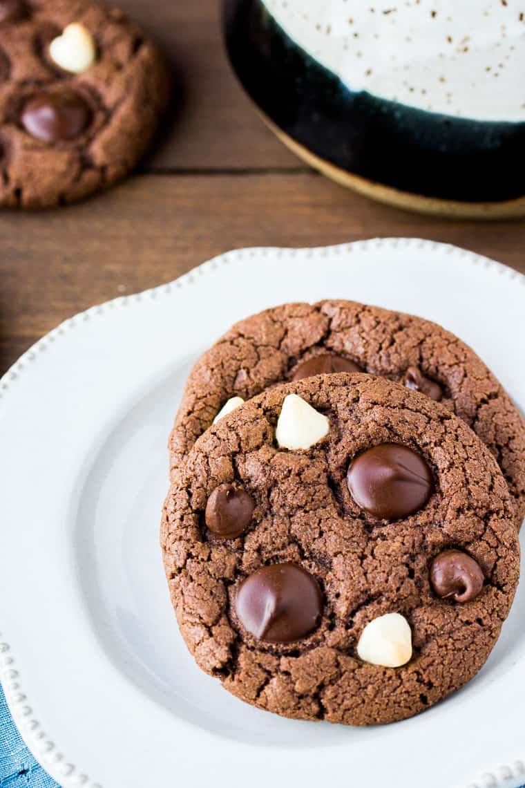 Close Up of 2 Gluten Free Triple Chocolate Cookies on a White Plate with another cookie and a black and tan mug in the background on a wood background
