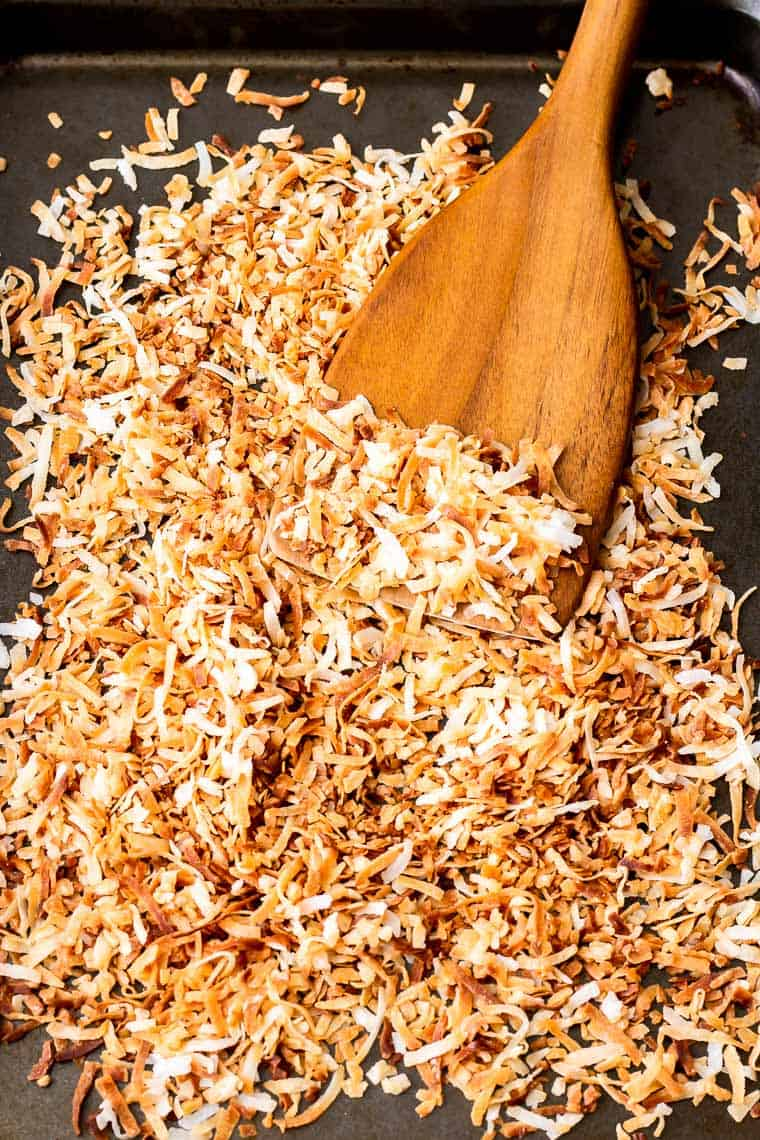 Overhead of a sheet pan with toasted coconut on it and a wood spatula