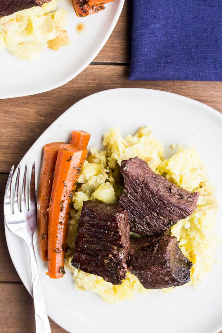 Red Wine Short Ribs from Overhead on White Plates with Mashed Potatoes and Carrots