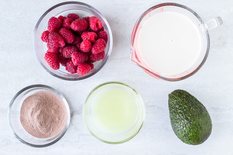 Ingredients to make a chocolate raspberry smoothie in glass bowls on a white background