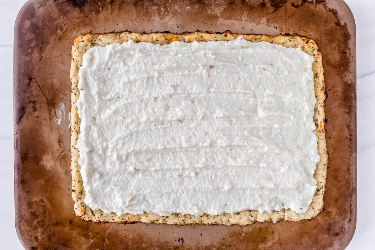 A pizza crust topped with ricotta cheese