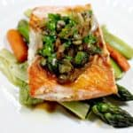 salmon on asparagus on a white plate