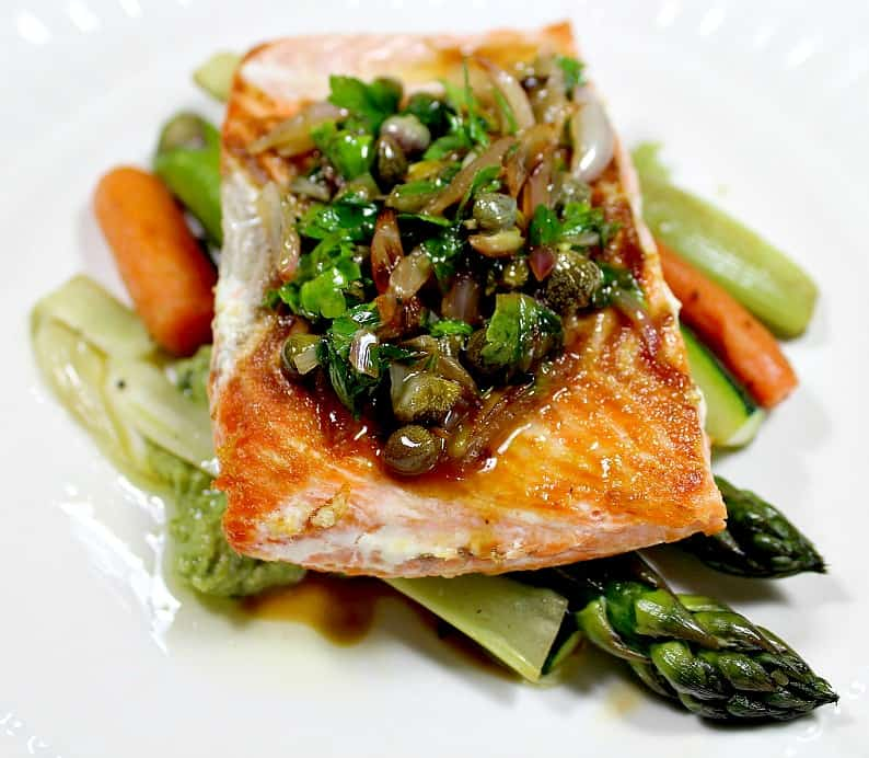 salmon on asparagus on a white plate