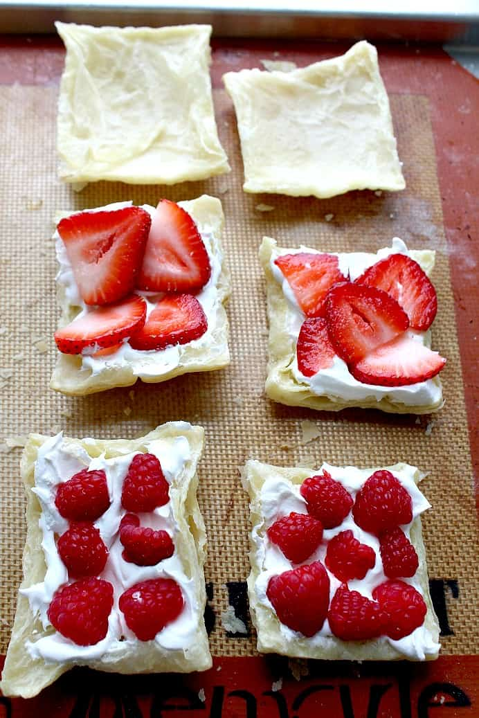 Puff Pastry squares broken open with 2 topped with whipped cream and strawberries, 2 topped with whipped cream and raspberries and 2 plain squares
