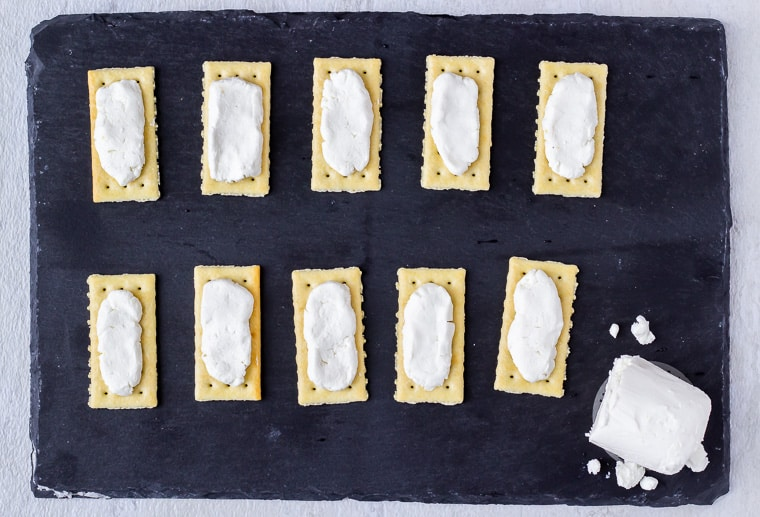 Goat Cheese on 10 crackers on a slate board with the remaining goat cheese log on the bottom right corner
