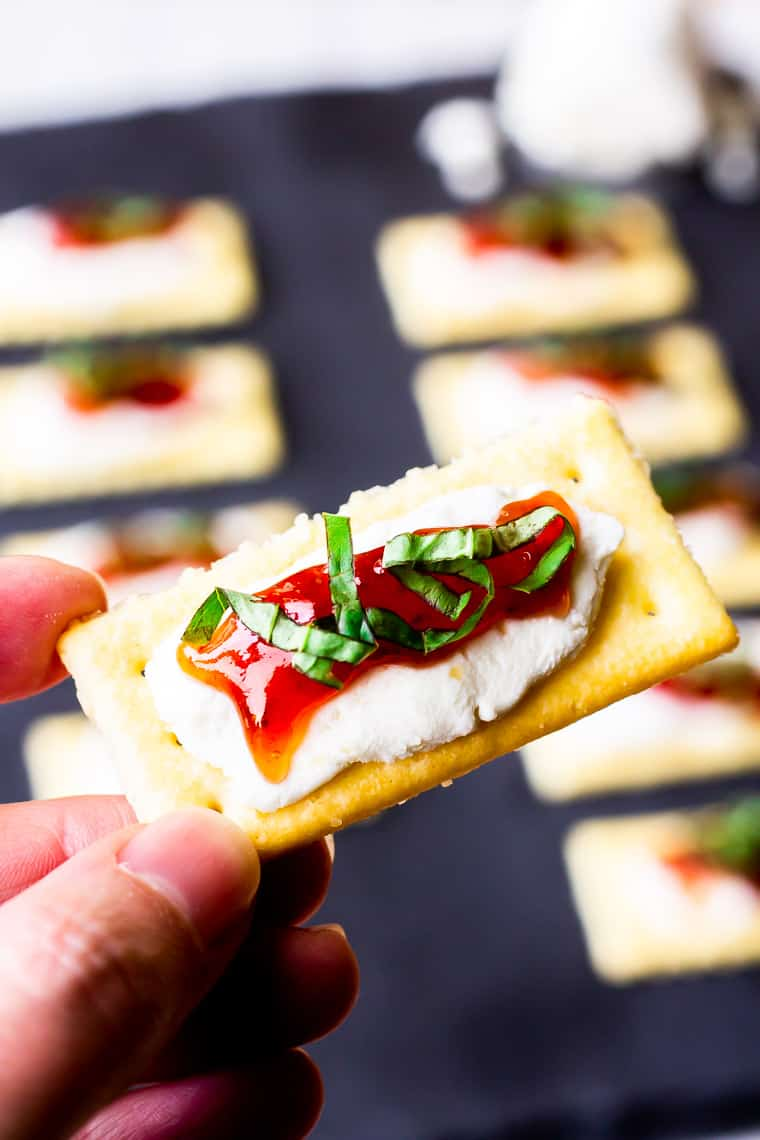 holding up a single strawberry goat cheese cracker with additional crackers on a piece of slate blurred in the background