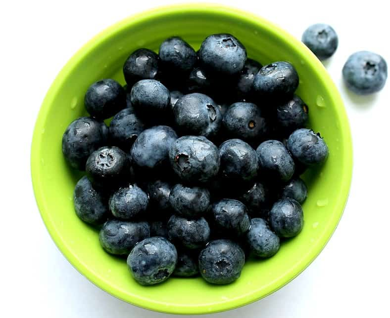 Close up of blueberries in a Green Bowl over a white background
