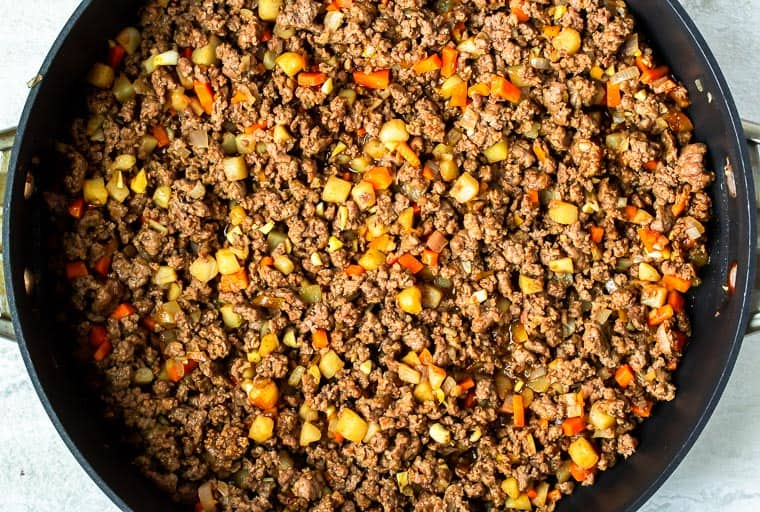 Ground beef mixed with Asian sauce in a black skillet