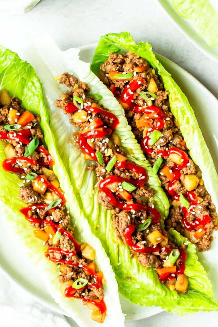 3 pieces of romaine lettuce filled with ground beef and vegetables on a white plate over a white background with part of a second plate with lettuce on it showing in the background