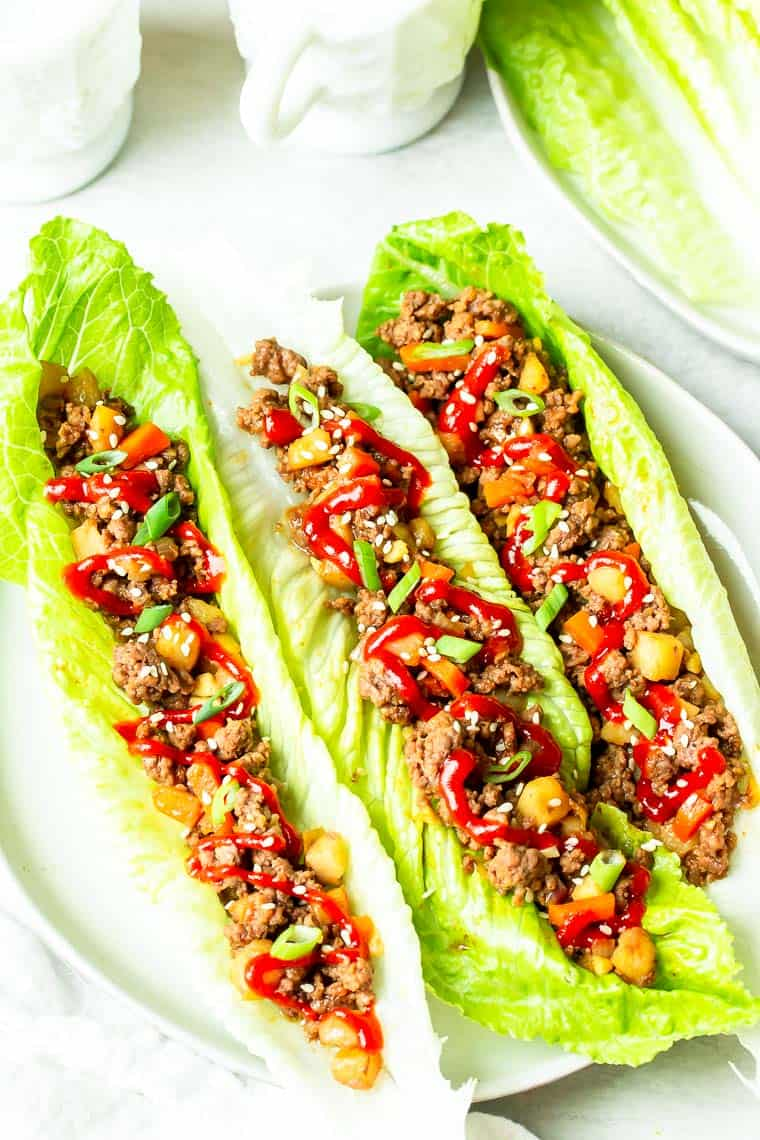 3 Ground Beef Lettuce Wraps on a white plate over a white background with extra lettuce on a white plate and a white cup in the background