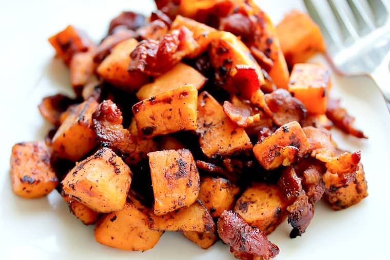 Close up of Maple Bacon Sweet Potato Hash with a fork on a white background