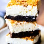 2 Butterfinger Cheesecake Bars stacked on top of each other on a white plate over a wood board with a blurred cloth napkin and fork in the background