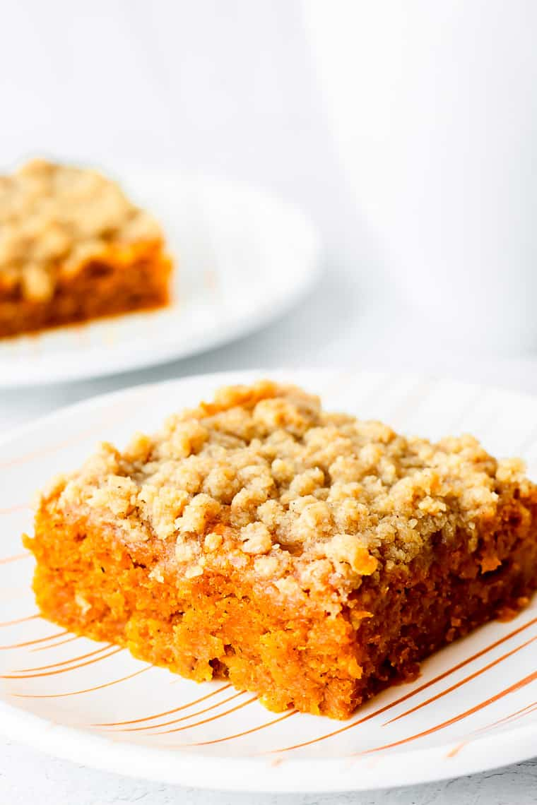 A slice of pumpkin spice coffee cake on a plate with a second slice and a white mug blurred behind it