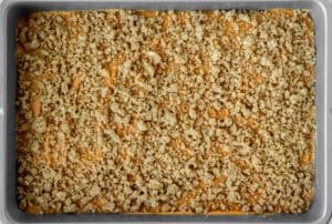 Pumpkin coffee cake in a pan with a crumb topping on it before baking