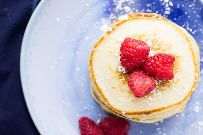 Overhead Of Pancakes on a Blue Plate with Raspberries and powdered sugar on Top and off to the side