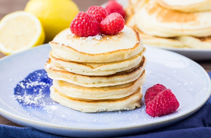 A Stack of Lemon Ricotta Pancakes on a Blue Plate with Raspberries and Lemons in the Background