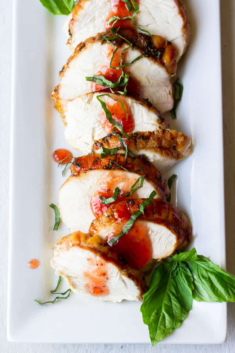 Slices of strawberry basil roasted turkey breast on a white serving tray with fresh basil leaves